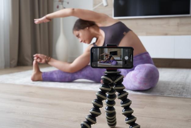 Młoda blogerka nagrywająca wideo sportowe w domu, robiąca jogę w salonie