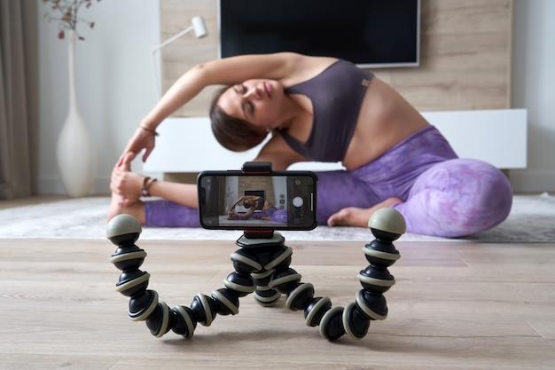 Młoda Blogerka Nagrywająca Wideo Sportowe W Domu, Robiąca Jogę W Salonie Premium Zdjęcia