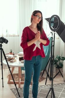 Młoda blogerka przygotowuje się do kręcenia wideo do vloga, plecy