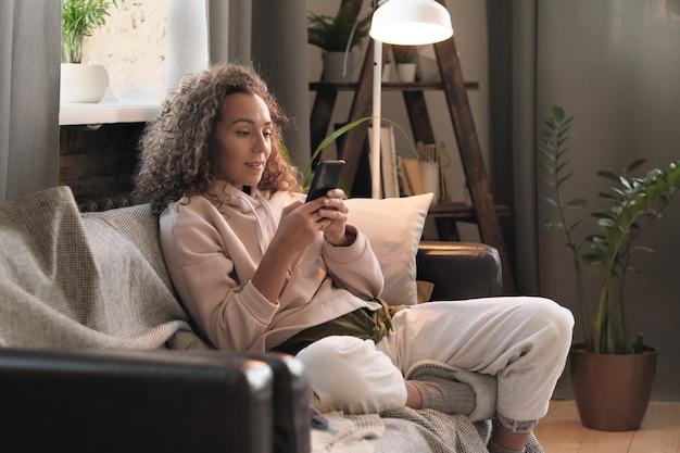 Młoda blogerka siedzi na kanapie i pracuje online na swoim telefonie komórkowym w domu