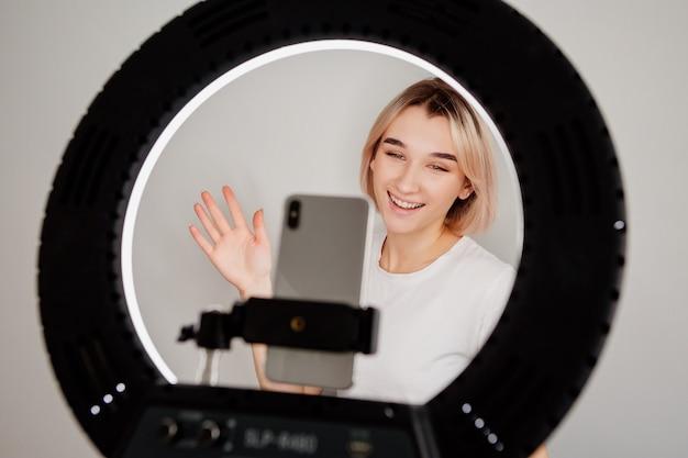 Młoda blogerka transmituje na żywo online w domu z lampą pierścieniową i smartfonem