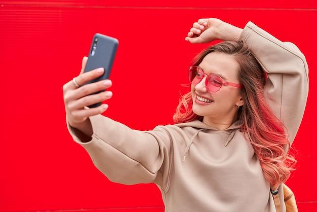 Młoda blogerka z farbowanymi na różowo włosami, stojąca w pobliżu czerwonej ściany i robiąca selfie za pomocą smartfona
