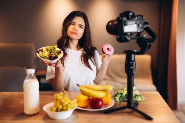 Młoda blogerka zdrowej żywności gotuje świeżą wegańską sałatkę z owoców i mówi nie słodyczom w studio kuchennym