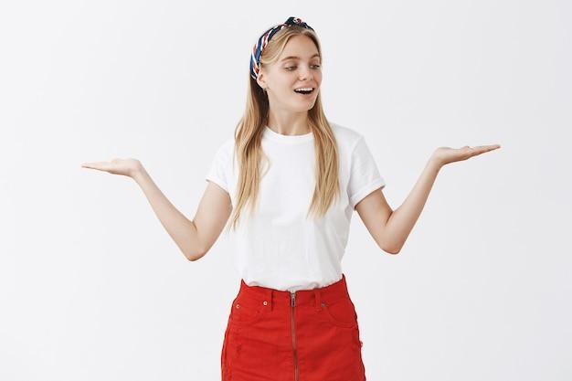 Młoda blond dziewczyna pozuje na białej ścianie