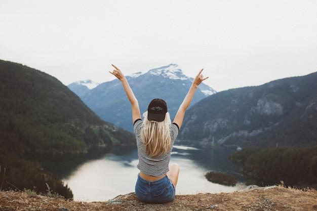 Młoda blond dziewczyna siedzi na klifie, podziwiając widok na góry i jezioro