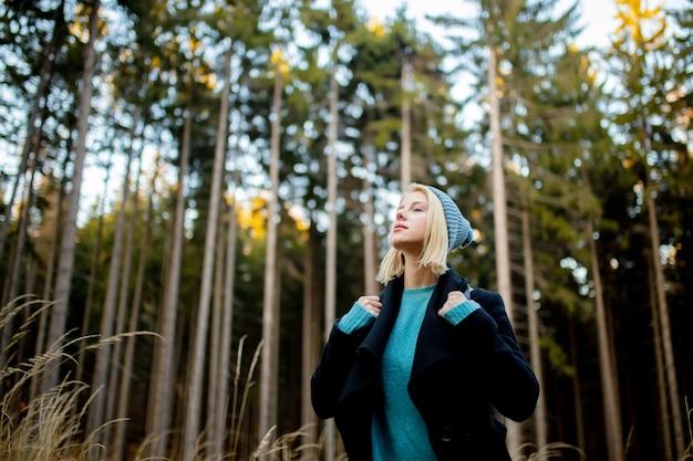 Młoda blond dziewczyna w lesie w czasie zachodu słońca
