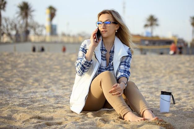 Młoda blond elegancka kobieta na plaży rozmawia przez jej telefon komórkowy.