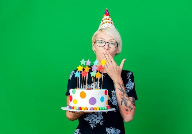 Młoda blond impreza w okularach i czapce urodzinowej trzyma tort urodzinowy z gwiazdami, trzymając rękę na ustach, patrząc na kamerę odizolowaną na zielonym tle z miejscem na kopię