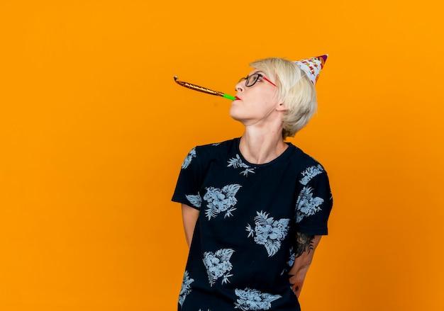 Młoda blond impreza w okularach i czapce urodzinowej, trzymając ręce za plecami, obracając głowę w bok, dmuchając dmuchawą imprezową na białym tle na pomarańczowym tle z miejscem na kopię