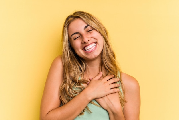 Młoda blond kaukaska kobieta odizolowana na żółtym tle ma przyjazny wyraz, przyciskając dłoń do klatki piersiowej. koncepcja miłości.