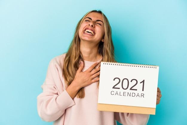 Młoda blond kaukaska kobieta z kalendarzem na białym tle śmieje się głośno trzymając rękę na klatce piersiowej.