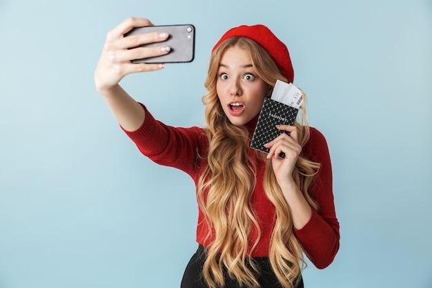 Młoda blond kobieta 20s trzyma paszport i bilet podróżny podczas robienia zdjęcia selfie na telefon komórkowy na białym tle