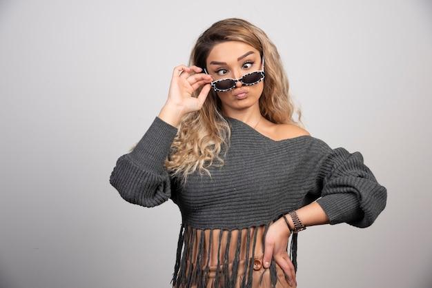 Młoda blond kobieta bawi się w okularach na szarym tle.