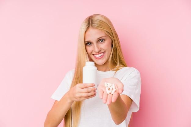 Młoda blond kobieta biorąc kilka tabletek na białym tle