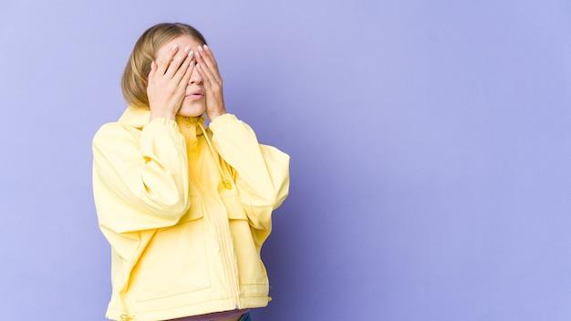 Młoda blond kobieta boi się zasłaniających oczy rękami.