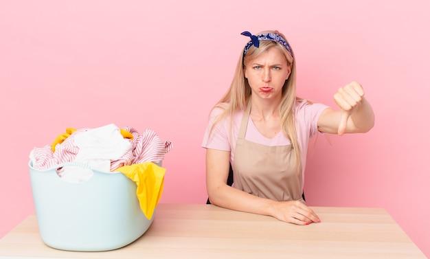 Młoda blond kobieta czuje krzyż, pokazując kciuk w dół. koncepcja prania ubrań