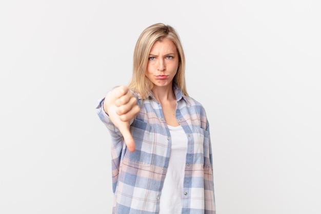 Młoda blond kobieta czuje krzyż, pokazując kciuk w dół