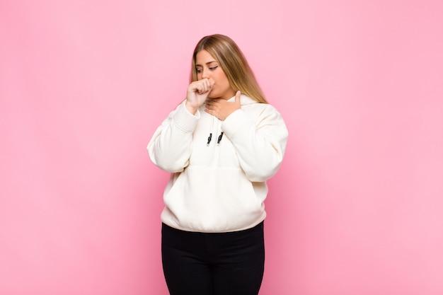 Młoda blond kobieta czuje się chora z bólem gardła i objawami grypy, kaszel z ustami pokrytymi płaską ścianą