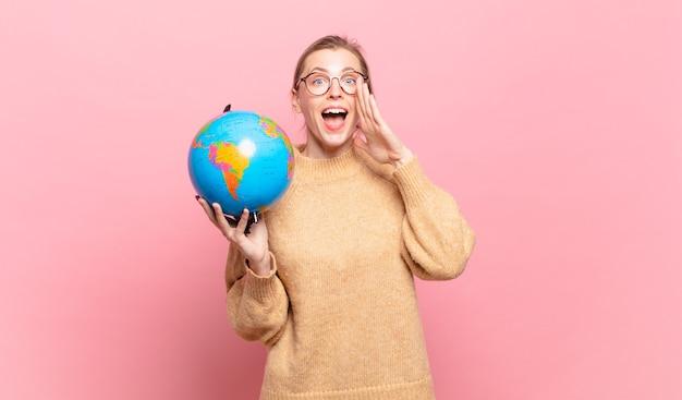 Młoda blond kobieta czuje się szczęśliwa, podekscytowana i pozytywna, wydając wielki okrzyk z rękami przy ustach, wołając. koncepcja świata