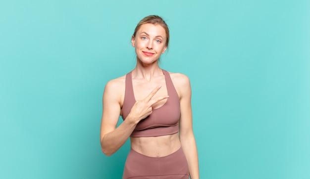 Młoda blond kobieta czuje się szczęśliwa, pozytywna i odnosząca sukcesy, z ręką tworzącą kształt litery v nad klatką piersiową, pokazując zwycięstwo lub pokój. koncepcja sportu