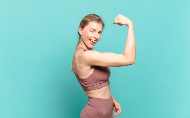 Młoda blond kobieta czuje się szczęśliwa, usatysfakcjonowana i potężna, napina sylwetkę i umięśnione bicepsy, wygląda na silną po siłowni. koncepcja sportu