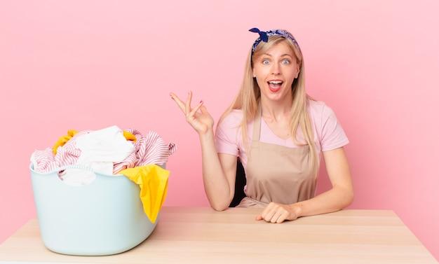 Młoda blond kobieta czuje się szczęśliwa, zaskoczona, gdy zdaje sobie sprawę z rozwiązania lub pomysłu. koncepcja prania ubrań