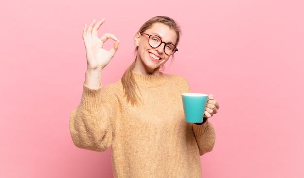 Młoda blond kobieta czuje się szczęśliwa, zrelaksowana i usatysfakcjonowana, okazując aprobatę dobrym gestem, uśmiechając się. koncepcja kawy