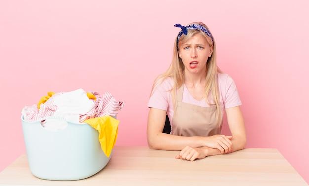 Młoda blond kobieta czuje się zdziwiona i zdezorientowana. koncepcja prania ubrań