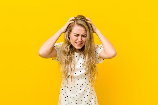 Młoda blond kobieta czuje się zestresowana i sfrustrowana, podnosząc ręce do głowy, czując się zmęczona, nieszczęśliwa iz migreną na żółtej ścianie