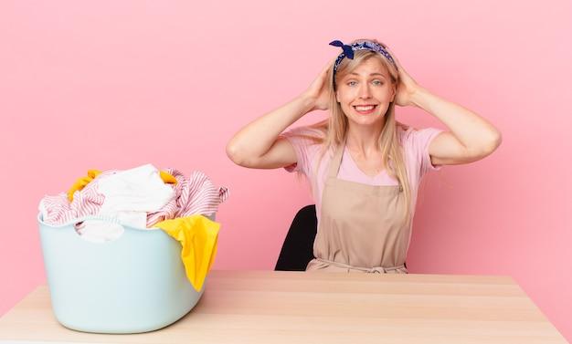 Młoda blond kobieta czuje się zestresowana, niespokojna lub przestraszona, z rękami na głowie. koncepcja prania ubrań