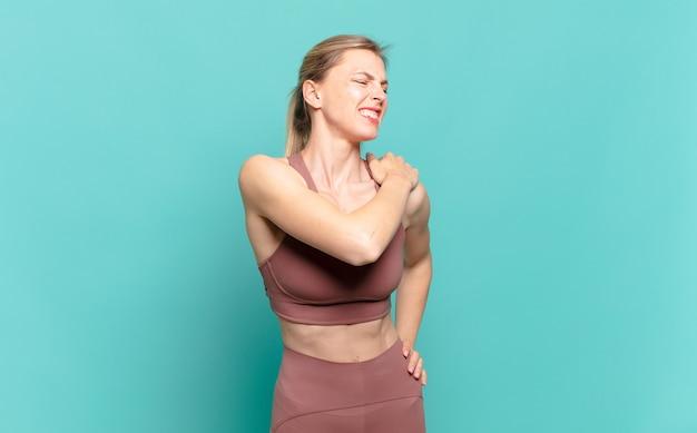 Młoda blond kobieta czuje się zmęczona, zestresowana, niespokojna, sfrustrowana i przygnębiona, cierpi na bóle pleców lub karku. koncepcja sportu