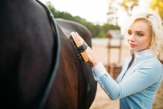 Młoda blond kobieta dba o włosy brązowego konia.