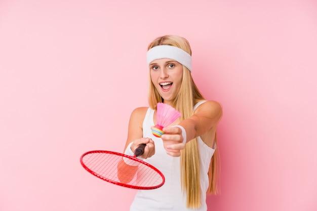 Młoda blond kobieta gra w badmintona na białym tle