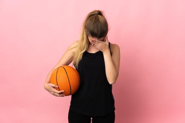 Młoda blond kobieta gra w koszykówkę na różowo z wyrazem zmęczenia i choroby