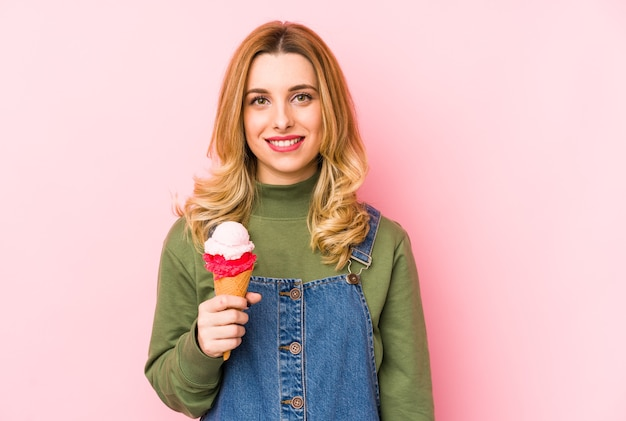 Młoda blond kobieta jedzenie lodów na białym tle szczęśliwy, uśmiechnięty i wesoły.