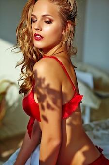 Młoda blond kobieta jest ubranym czerwonego bielizny obsiadanie na łóżku w ranku