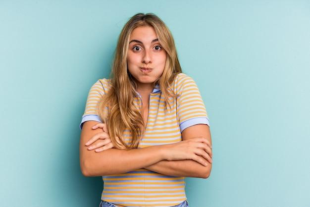 Młoda blond kobieta kaukaski na białym tle na niebieskim tle dmucha w policzki, ma zmęczony wyraz. koncepcja wyraz twarzy.