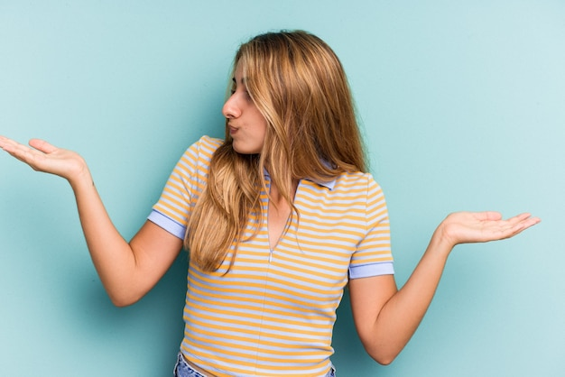Młoda blond kobieta kaukaski na białym tle na niebieskim tle mylić i wątpliwe wzruszając ramionami, aby trzymać miejsce na kopię.