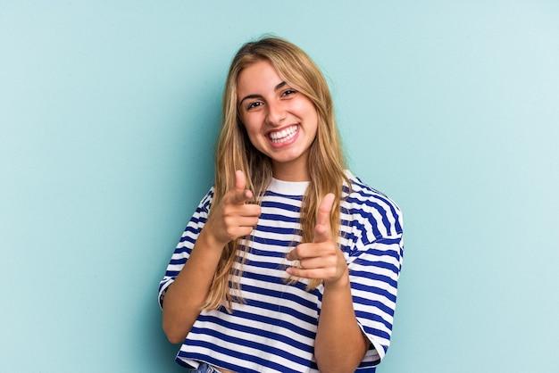 Młoda blond kobieta kaukaski na białym tle na niebieskim tle, wskazując do przodu palcami.