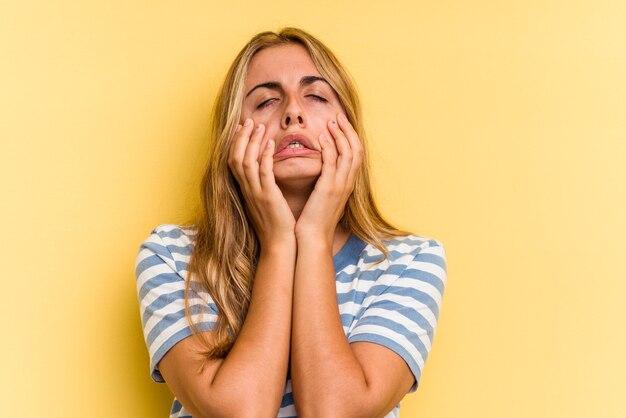 Młoda blond kobieta kaukaski na białym tle na żółtym tle marudzenie i płacz niepocieszony.