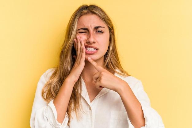 Młoda blond kobieta kaukaski na białym tle na żółtym tle o silny ból zębów, ból trzonowy.