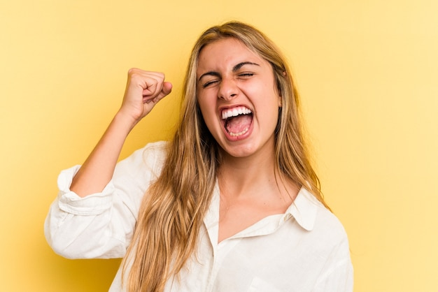 Młoda blond kobieta kaukaski na białym tle na żółtym tle świętuje zwycięstwo, pasję i entuzjazm, szczęśliwy wyraz.