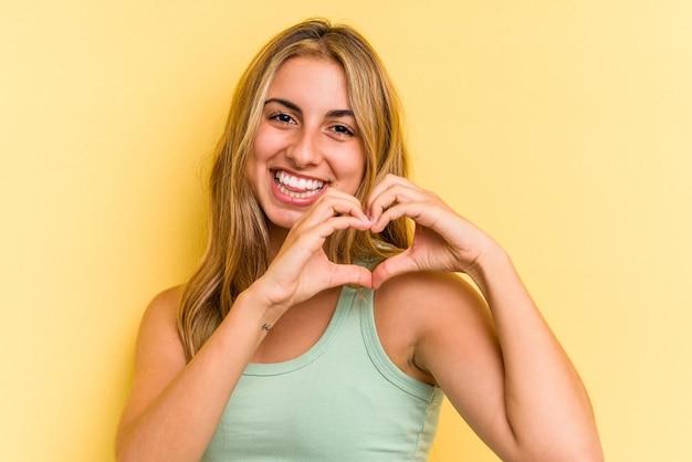 Młoda blond kobieta kaukaski na białym tle na żółtym tle, uśmiechając się i pokazując kształt serca rękami.