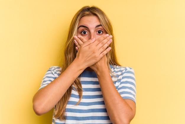 Młoda blond kobieta kaukaski na białym tle na żółtym tle w szoku obejmujące usta rękami.
