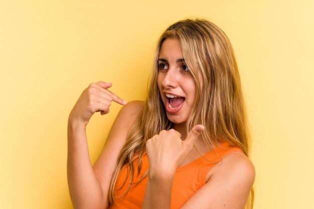 Młoda blond kobieta kaukaski na białym tle na żółtym tle zaskoczony, wskazując palcem, uśmiechając się szeroko.