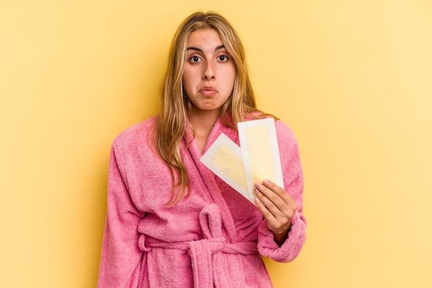 Młoda blond kobieta kaukaski ubrana w szlafrok, trzymająca opaski do depilacji na białym tle na żółtym tle, wzrusza ramionami i otwiera oczy zdezorientowana.