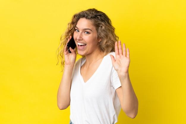 Młoda blond kobieta korzystająca z telefonu komórkowego na białym tle, pozdrawiając ręką ze szczęśliwym wyrazem twarzy