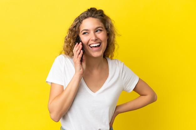 Młoda blond kobieta korzystająca z telefonu komórkowego na żółtym tle pozuje z rękami na biodrach i uśmiecha się
