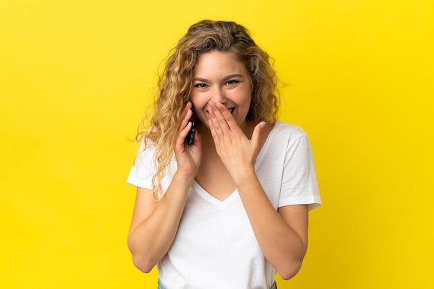 Młoda blond kobieta korzystająca z telefonu komórkowego na żółtym tle szczęśliwa i uśmiechnięta zakrywająca usta dłonią