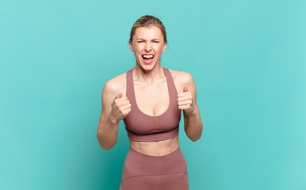 Młoda blond kobieta krzyczy agresywnie z rozdrażnionym, sfrustrowanym, gniewnym spojrzeniem i zaciśniętymi pięściami, czując się wściekły. koncepcja sportu